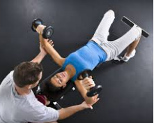 Trainer training woman in gym