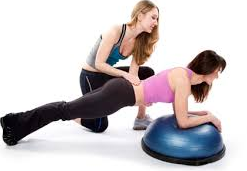 trainer helping woman on gym ball