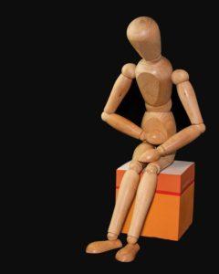 Wood doll sitting on box