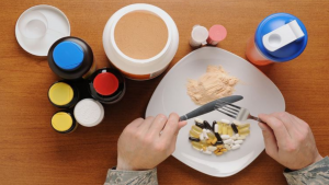 plate with supplements and hands with fork & knife